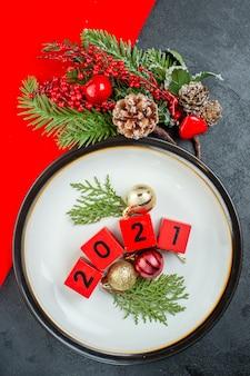 Vista superior de números de acessórios de decoração em um prato e cone de conífera de ramos de abeto em uma mesa escura