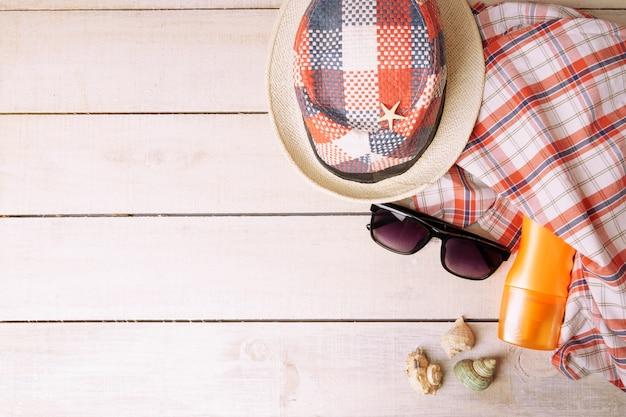 Vista superior de óculos de sol, conchas, protetor solar, toalha e chapéus