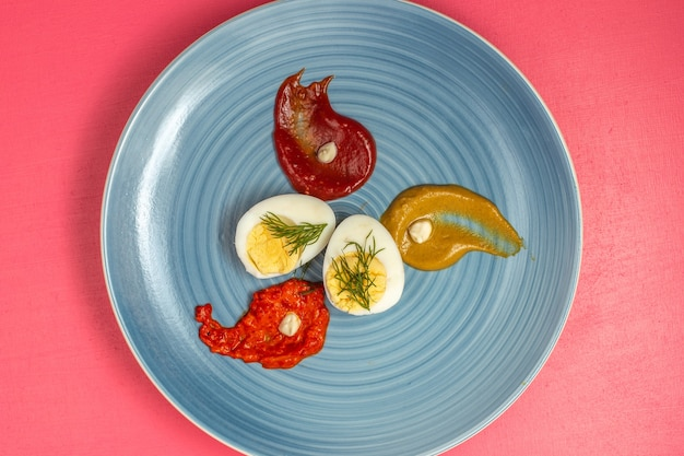 Vista superior de ovo cozido com ketchup e mostarda dentro do prato na parede rosa