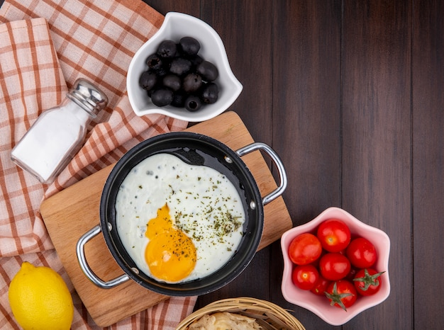 Vista superior de ovo frito em uma frigideira na mesa de madeira da cozinha com azeitonas pretas na tigela branca e tomates na toalha xadrez e madeira