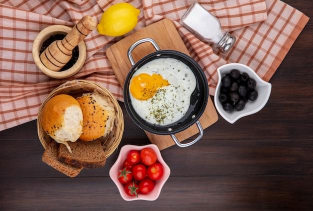 Vista superior de ovo frito na frigideira na mesa de madeira da cozinha com um bcuket de pães, azeitonas pretas, tomates