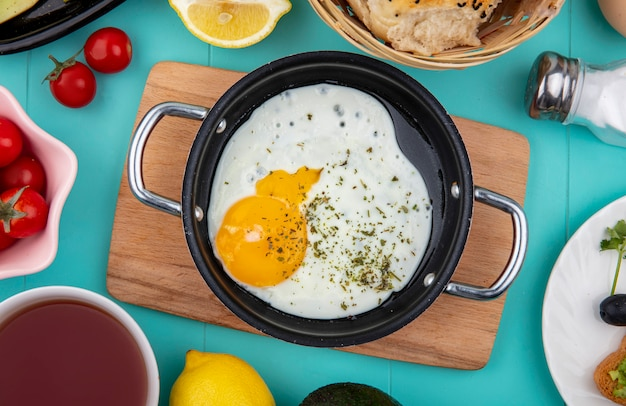 Vista superior de ovo frito na frigideira na placa de madeira da cozinha com limão e um balde de pães no azul