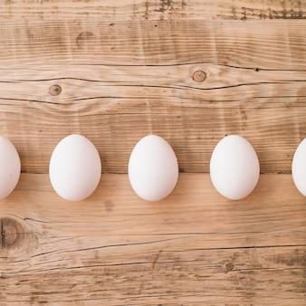 Vista superior de ovos brancos em um fundo de madeira