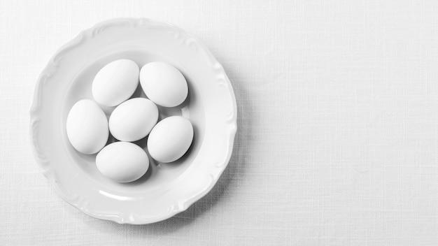 Vista superior de ovos brancos no prato com cópia-espaço
