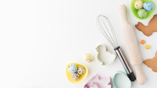 Vista superior de ovos coloridos e utensílios de cozinha, com espaço de cópia