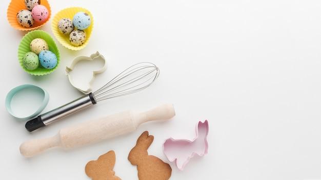 Vista superior de ovos coloridos para a páscoa com utensílios de cozinha e espaço de cópia