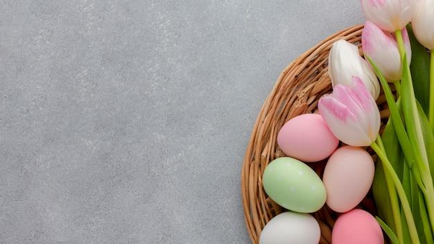 Vista superior de ovos coloridos para a páscoa na cesta com tulipas