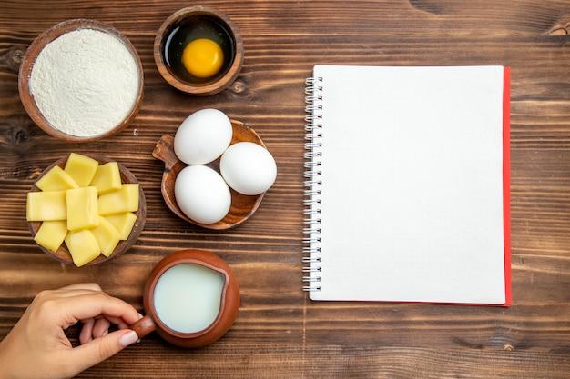 Vista superior de ovos crus com farinha de queijo e leite na superfície de madeira, produto, massa de ovo, comida crua