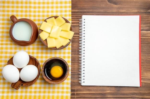 Vista superior de ovos crus com queijo e leite na superfície de madeira.