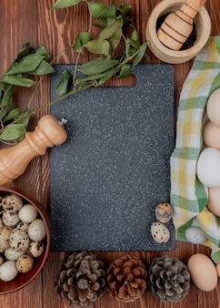 Vista superior de ovos de codorna em uma tigela de madeira com folhas com pinhas em um fundo de madeira com espaço de cópia