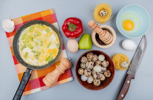 Vista superior de ovos de codorna em uma tigela de madeira com ovos fritos em uma frigideira com pimentão com faca no fundo branco