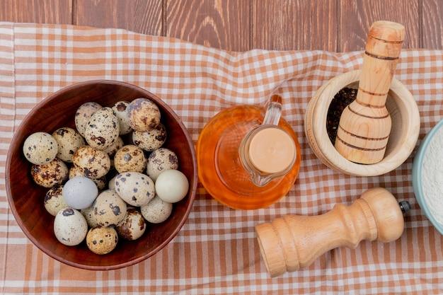 Vista superior de ovos de codorna em uma tigela de madeira com vinagre em uma toalha xadrez amarela sobre um fundo de madeira