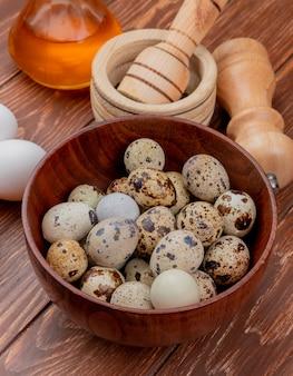 Vista superior de ovos de codorna frescos em uma tigela de madeira com ovos de galinha branca com vinagre em um fundo de madeira