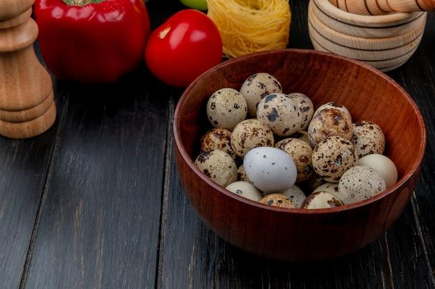 Vista superior de ovos de codorna pequenos em uma tigela de madeira com um pimentão vermelho sobre um fundo de madeira