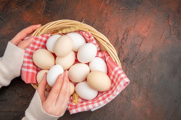 Vista superior de ovos de galinha branca dentro da cesta com uma toalha na mesa escura