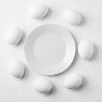 Vista superior de ovos de galinha branca na mesa com prato
