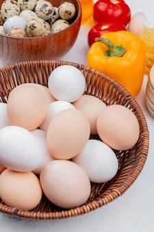 Vista superior de ovos de galinha em um balde com ovos de codorna em uma tigela de madeira com legumes em fundo branco