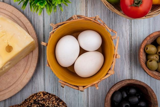 Vista superior de ovos de galinha em uma cesta com queijo de tomate e azeitonas em fundo cinza