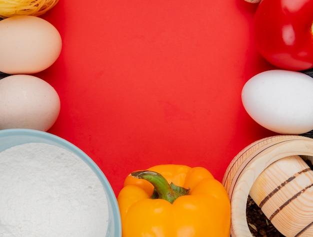 Vista superior de ovos de galinha fresca com farinha em uma tigela azul sobre fundo vermelho, com espaço de cópia