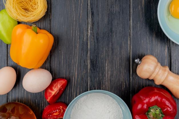 Vista superior de ovos de galinha fresca com uma fatia de tomate com pimentos coloridos em um fundo de madeira com espaço de cópia