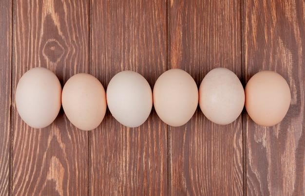 Vista superior de ovos de galinha fresca, dispostos em linha em um fundo de madeira