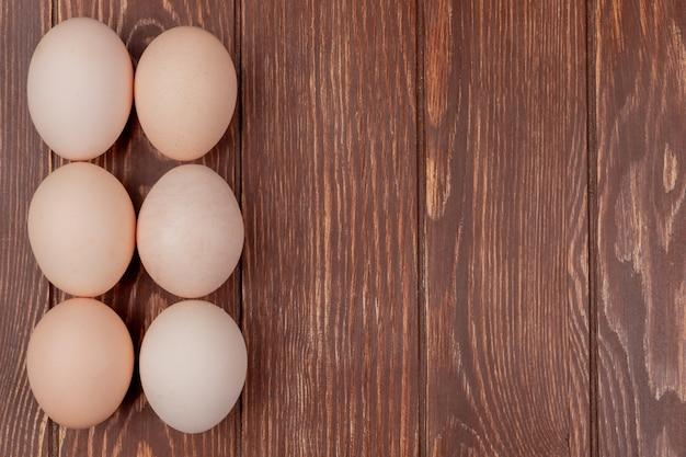 Vista superior de ovos de galinha fresca, dispostos em um fundo de madeira com espaço de cópia