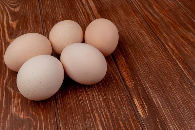 Vista superior de ovos de galinha fresca, isolados em um fundo de madeira