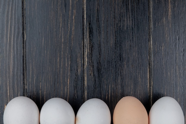 Vista superior de ovos de galinha frescos e saudáveis, dispostos em uma linha em um fundo de madeira com espaço de cópia