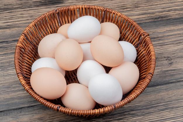 Vista superior de ovos de galinha frescos e saudáveis em um balde em um fundo de madeira