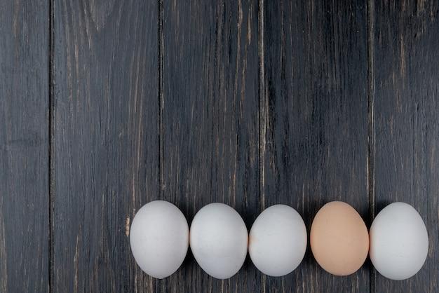 Vista superior de ovos de galinha frescos e saudáveis em um fundo de madeira com espaço de cópia