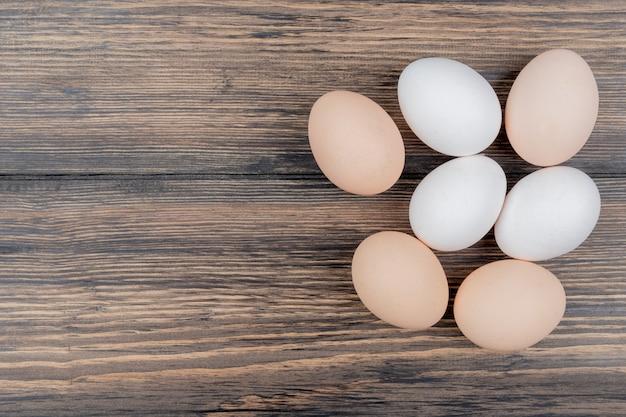 Vista superior de ovos de galinha, isolados em um fundo de madeira com espaço de cópia