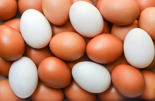 Vista superior de ovos de galinha marrom e ovos de pato branco para o fundo