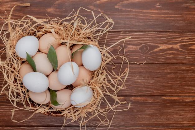 Vista superior de ovos de galinha no ninho com folhas em um fundo de madeira com espaço de cópia
