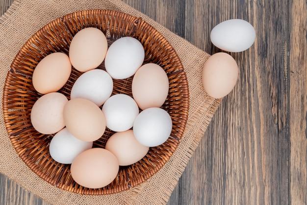 Vista superior de ovos de galinha saudáveis e frescos em um balde no pano de saco em um fundo de madeira