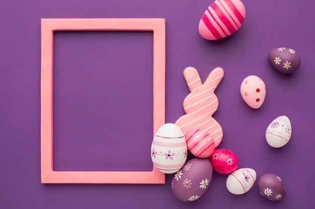 Vista superior de ovos de páscoa coloridos com moldura e coelho