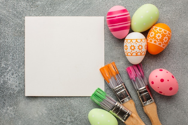Vista superior de ovos de páscoa coloridos com pincéis e papel