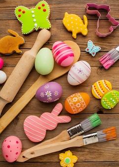 Vista superior de ovos de páscoa coloridos com utensílios de cozinha e formas de coelho