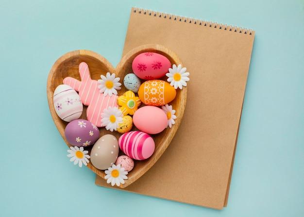 Vista superior de ovos de páscoa coloridos em prato em forma de coração com caderno