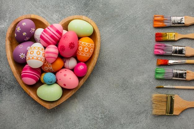 Vista superior de ovos de páscoa coloridos em um prato em forma de coração com uma variedade de pincéis