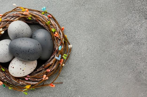 Vista superior de ovos de páscoa coloridos em uma cesta com espaço de cópia