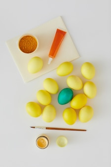 Vista superior de ovos de páscoa coloridos naturais com detalhes em verde e pincel com composição mínima em fundo branco, copie o espaço