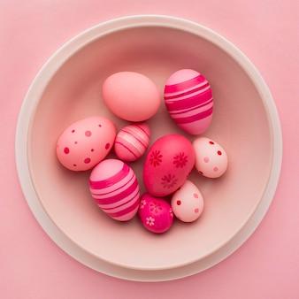 Vista superior de ovos de páscoa coloridos no prato