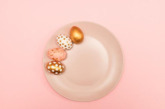 Vista superior de ovos de páscoa decorados rosa, brancos e dourados na chapa rosa sobre fundo rosa. cenário de férias na moda