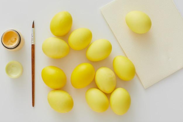 Vista superior de ovos de páscoa em amarelo pastel com pincel definido em composição mínima em fundo branco, copie o espaço