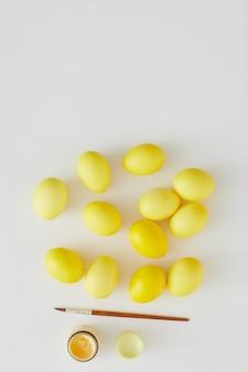 Vista superior de ovos de páscoa em amarelo pastel com pincel representado em composição mínima em fundo branco, copie o espaço