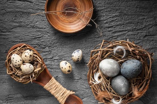 Vista superior de ovos de páscoa em um ninho de pássaro e uma colher de pau sobre uma lousa