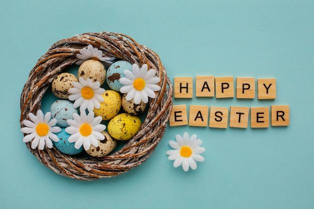 Vista superior de ovos de páscoa em uma cesta com flores de saudação e camomila