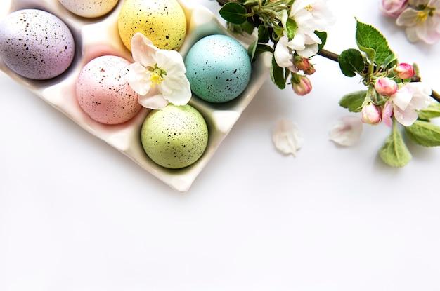 Vista superior de ovos de páscoa pintados e bandeja de ovos na mesa branca
