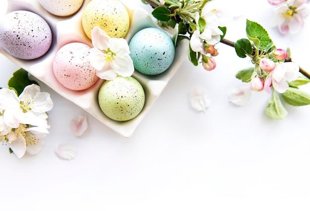 Vista superior de ovos de páscoa pintados e bandeja de ovos na parede branca