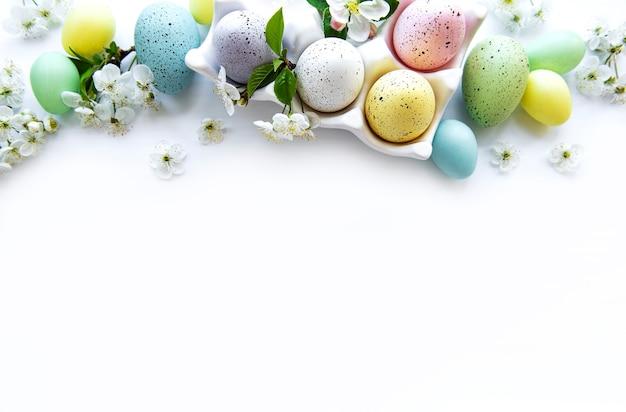 Vista superior de ovos de páscoa pintados e bandeja de ovos na superfície de madeira branca